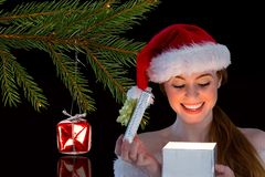 Happy woman in santa hat opening her gift box in night Royalty Free Stock Photo