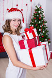 Happy woman in santa hat with presents near Christmas tree Royalty Free Stock Images