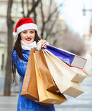 Happy woman in Santa hat with purchases Stock Image