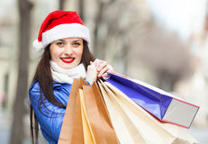 Happy woman in Santa hat with purchases Stock Photo