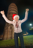 Happy woman in Santa hat rejoicing near Leaning Tower of Pisa Stock Photography