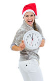 Happy woman in Santa hat showing clock Royalty Free Stock Photo