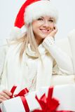 Happy woman in santa hat sitting near sofa Stock Photo
