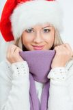 Happy woman in santa hat sitting near sofa Royalty Free Stock Image