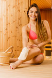 Happy woman in sauna with exfoliating glove. Happy young woman in wood finnish spa sauna massaging skin with exfoliating glove. Girl in bikini relaxing Royalty Free Stock Photos