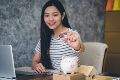 Happy woman saving money in a piggy bank Stock Photos