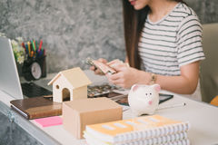 Happy woman saving money in a piggy bank Royalty Free Stock Images