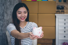 Happy woman saving money in a piggy bank Royalty Free Stock Photos