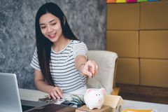 Happy woman saving money in a piggy bank Royalty Free Stock Photo