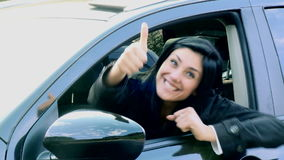 Happy woman saying hello from car thumb up stock footage