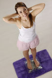 Happy woman on scales satisfied for weight loss Stock Images