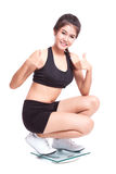 Happy woman with scales and showing thumbs up Stock Photo