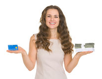 Happy woman scaling credit card and money packs Royalty Free Stock Image