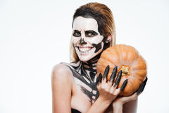Happy woman with scared halloween makeup holding pumpkin and smiling Stock Photo