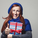 Happy woman. In scarf showing thumbs up and holding a gift box Royalty Free Stock Photography