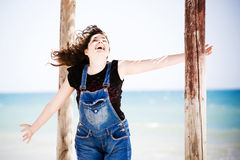 Happy woman by sea. Happy young woman with outstretched arms in dungaree with sea in background Royalty Free Stock Image