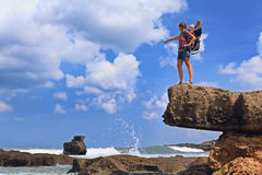 Happy woman on sea cliff with child in backpack carrier Royalty Free Stock Image