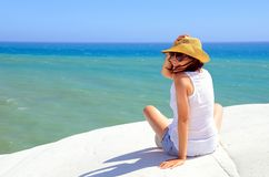 Happy woman at the sea side. Happy woman sitting on the sea side holding his hat Royalty Free Stock Images