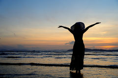 Happy Woman in Sea Sunset at beach in Thailand Stock Photography