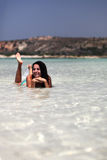 Happy woman in sea water. Young happy woman laying in shallow sea waterin Crete Grece Royalty Free Stock Images