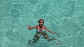 The happy woman in the sea waves to us greeting a hand Royalty Free Stock Image