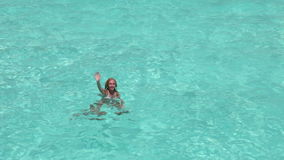 The happy woman in the sea waves to us greeting a hand stock video footage