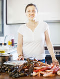 Happy woman  with seafood in  kitchen Royalty Free Stock Image