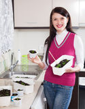 Happy woman with  seedlings at home kitchen Royalty Free Stock Photos