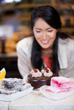 Happy woman selecting desserts from display Royalty Free Stock Images