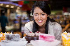 Happy woman selecting desserts from display Stock Image