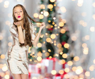 Happy woman sending blowkiss over christmas lights Stock Image