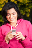Happy woman sending or reading sms on mobile phone Stock Image