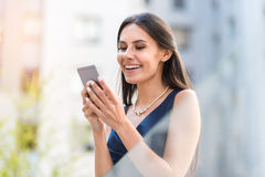 Happy woman sending sms by phone. Lady expressing gladness while writing message by mobile on street stock photography