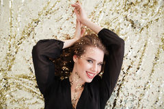 Happy woman with sequins on her face lying and smiling Stock Photo