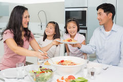 Happy woman serving food for the family in kitchen Royalty Free Stock Photo