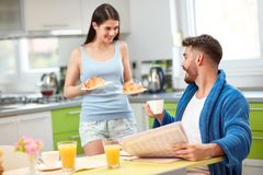 Woman serving rich breakfast to husband royalty free stock image