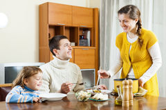 Happy woman serving soup her husband and child Royalty Free Stock Images