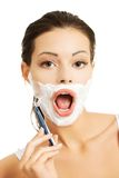 Happy woman shaving her face Stock Image