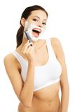 Happy woman shaving her face Stock Images