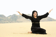 Happy woman in shawl sitting on sand Royalty Free Stock Photos