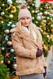 Happy woman in a sheepskin coat and knitted hat. Happy Beautiful blonde woman in a sheepskin coat and knitted hat in the center of the Christmas courtyard stock images