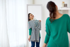 Happy woman with shirt looking to mirror at home. Clothing, wardrobe, fashion, style and people concept - happy woman with shirt looking to mirror at home Royalty Free Stock Photos