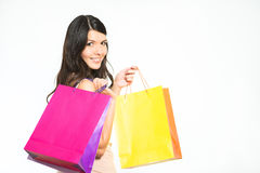 Happy woman shopper with colorful bags. Full of her recent purchases turning to smile at the camera with a look of satisfaction and pleasure royalty free stock photo