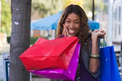 Happy Woman Shopping. Attractive young happy African American woman walking in an urban city environment and carrying shopping bags Stock Photography
