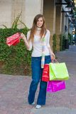 Happy Woman Shopping. Attractive young happy woman with red hair walking in an urban city environment and carrying shopping bags Royalty Free Stock Photography