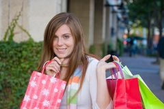 Happy Woman Shopping. Attractive young happy woman with red hair walking in an urban city environment and carrying shopping bags Stock Photo