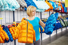 Happy woman shopping for baby jacket in shop Royalty Free Stock Photo
