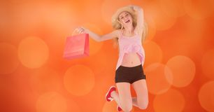 Happy woman with shopping bag jumping over bokeh Royalty Free Stock Photos