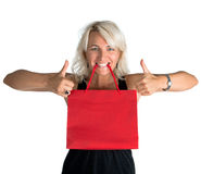 Happy woman with shopping bag in mouth and showing ok sign Royalty Free Stock Photo