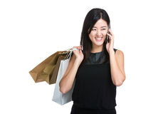 Happy woman with shopping bag and talk to mobile phone Royalty Free Stock Photography
